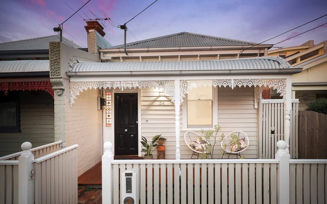 White weatherboard workers cottage. White timber fence and welcoming appearance.