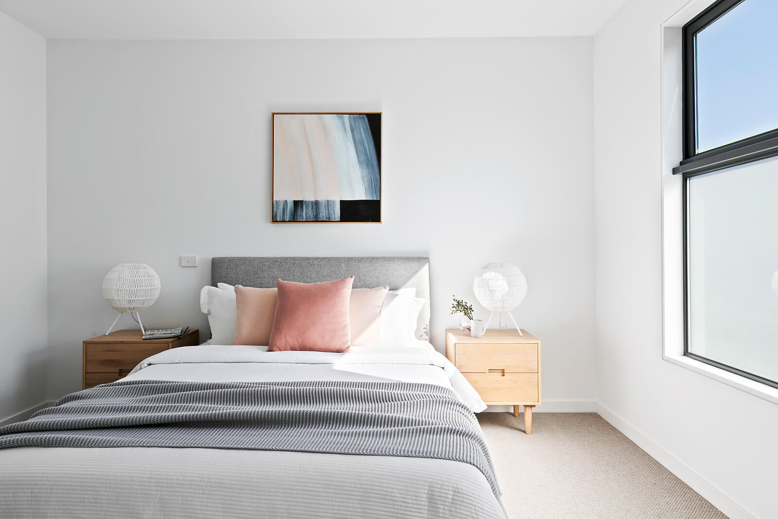 Bed with pink cushions, grey throw, white linen. Timber bedside tables with woven white table lamps. Grey bedhead with centred artwork above with hues of pink, blue and navy.