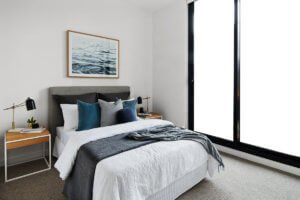 bedroom styled for sale with greys and blues, timber bedside tables and timber framed ocean artwork