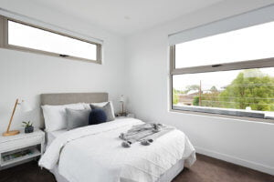 Light filled bedroom with fresh linen and grey throw